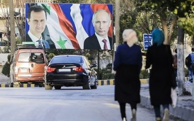 Syrians walking past a giant poster of Syrian President Bashar Assad (L) and his Russian counterpart Vladimir Putin (R) in the northern Syrian city of Aleppo, March 9, 2017. (AFP Photo/Joseph Eid/ File)