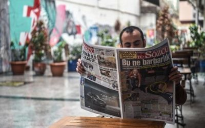 """A man reads a newspaper bearing a headline concerning diplomatic tensions between Turkey and The Netherlands, which translates as """"What a Barbarism"""" in Istanbul on March 13, 2017. (Ozan Kose/AFP)"""