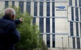A man walks past the logo of Israeli car tech firm Mobileye on the company's offices in Jerusalem on March 13, 2017. (AFP PHOTO / THOMAS COEX)