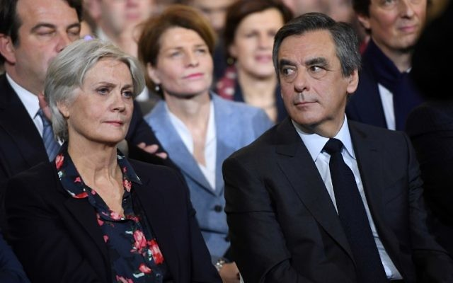This photo taken on January 29, 2017 in Paris shows French right wing candidate for the upcoming presidential election Francois Fillon (R) flanked by his wife Penelope (L), looking on during a campaign rally.(AFP PHOTO / Eric FEFERBERG)