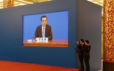 Two photographers take photos of Chinese Premier Li Keqiang as a live image of him is seen on a screen behind them during a press conference after the closing session of the National People's Congress in the Great Hall of the People in Beijing on March 15, 2017. (Greg Baker/AFP)