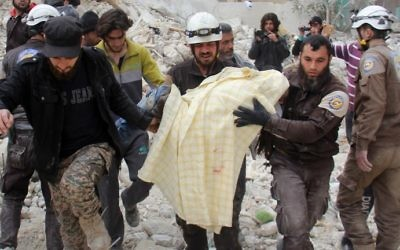 Members of the Syrian civil defense, known as the White Helmets, remove a victim from the rubble of a destroyed building following a reported air strike in the northwestern city of Idlib on March 15, 2017. (AFP PHOTO / Omar haj kadour)