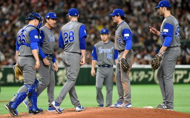 Israeli infielders and a coach gather around picher Josh Zeid (#28) in the bottom of the third inning during the World Baseball Classic Pool E second round match between Israel and Japan at Tokyo Dome in Tokyo on March 15, 2017. (AFP PHOTO / TORU YAMANAKA)