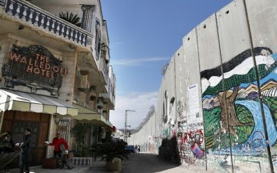 The Israeli controversial separation wall is seen in front of artist Banksy's newly opened Walled Off hotel in the Israeli occupied West Bank town of Bethlehem, on March 15, 2017. (Thomas Coex/AFP)
