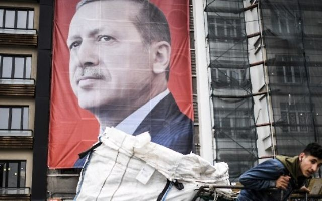 A man pulls a cart in front of a huge portrait of Turkish President Recep Tayyip Erdogan on Taksim Square in Istanbul on March 15, 2017. (AFP Photo/Bulent Kilic)