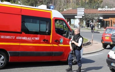 A policeman wearing a bulletproof vest stands near a firefighters vehicle on a road near the Tocqueville high school in the southern French town of Grasse, on March 16, 2017 following a shooting that left two people injured. (Valery Hache/AFP)