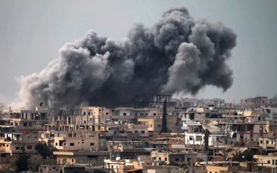 Illustrative: Smoke billows following reported air strikes on a rebel-held area in the southern city of Daraa, on March 16, 2017. (AFP Photo/Mohamad Abazeed)