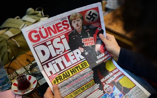 "A man reads an issue of Gunes, a Turkish pro-government daily newspaper, with on its front page German Chancellor Angela Merkel depicted in Nazi uniform with a Hitler-style mustache, labeling the German leader ""She Hitler"", on March 17, 2017 in Istanbul, Turkey. (AFP PHOTO / YASIN AKGUL)"