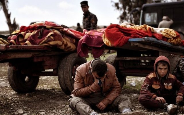 Relatives mourn as bodies of Iraqi residents of west Mosul killed in an airstrike targeting Islamic State jihadists are placed on carts and covered with blankets, March 17, 2017. (AFP/Aris Messinis)
