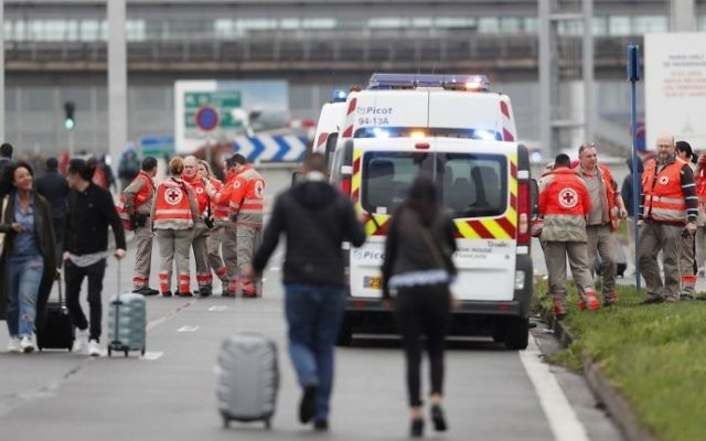 French Red Cross workers stand by as travelers are evacuated from Paris' Orly airport on March 18, 2017 following the shooting of a man by French security forces. (Benjamin CREMEL)