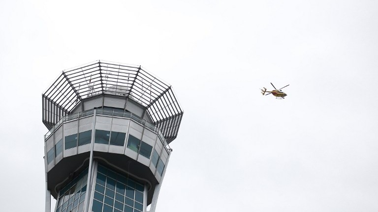 An helicopter flies near a control tower at the Paris' Orly airport on March 18, 2017 following the shooting of a man by French security forces. (AFP PHOTO / Benjamin CREMEL)