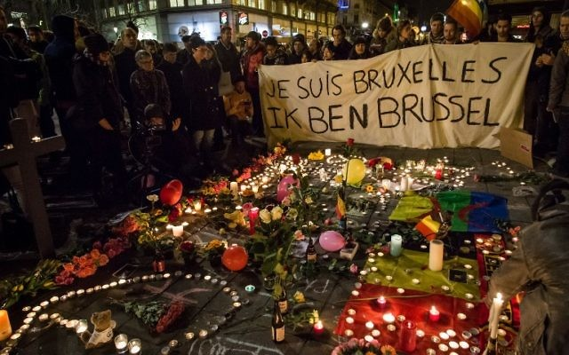 "People holding a banner reading in French and Flamish ""I AM BRUSSELS"" as they gather around floral tributes, candles, Belgian and peace flags and notes in front of the Bourse of Brussels, in tribute to the victims of Brussels,  March 22, 2016. (AFP Photo/Belga/Aurore Belot/Belgium OUT)"