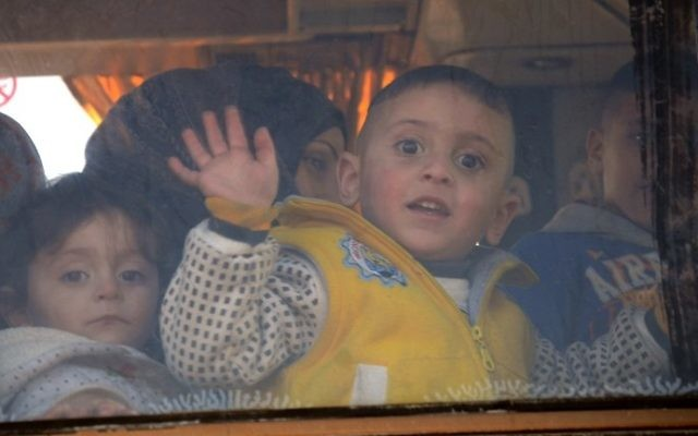 A child waves from the window of a bus as Syrians who were evacuated from Waer, the last opposition-held district of Homs, arrive in the northern Syrian town of al-Bab on March 19, 2017. (AFP PHOTO / Nazeer al-Khatib)