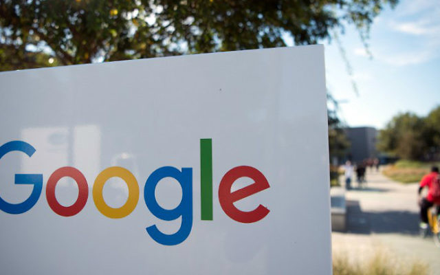 This file photo taken on November 4, 2016 shows a man riding a bike past a Google sign and logo at the Googleplex in Menlo Park, California. (Josh Edelson/AFP)