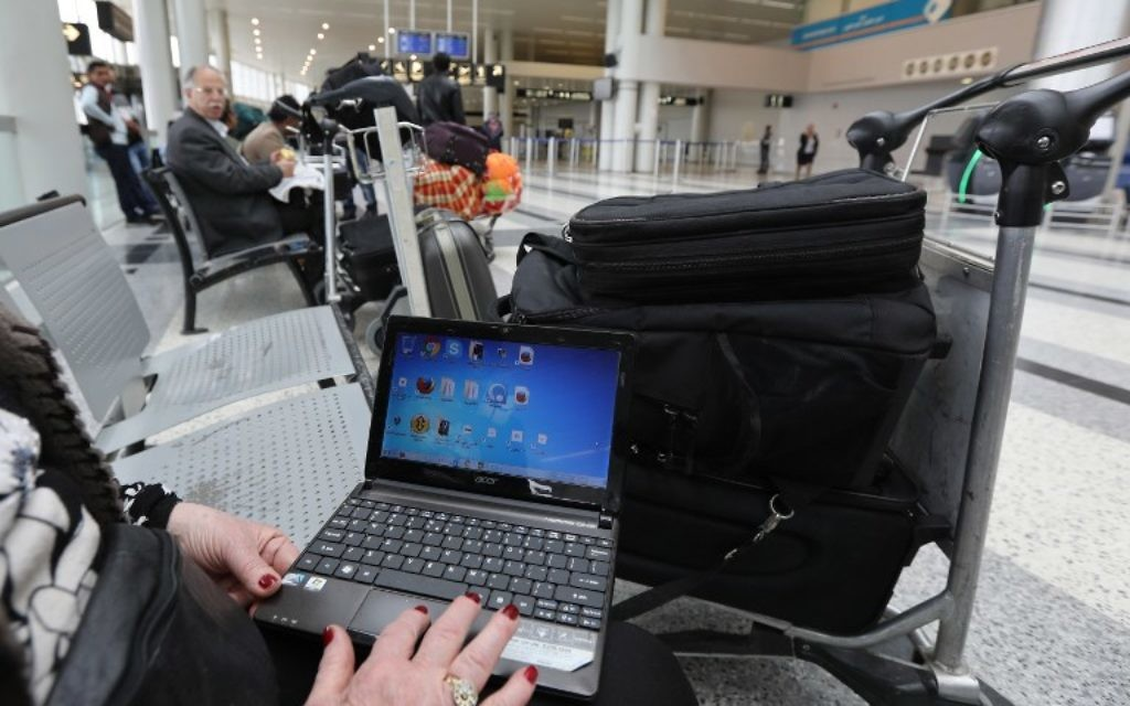 A Syrian woman travelling to the United States through Amman opens her laptop before checking in at Beirut international airport on March 22,2017 (AFP PHOTO / ANWAR AMRO)