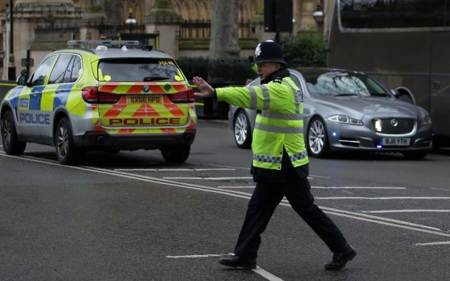 A police officer stops traffic as the Jaguar car of British Prime Minister Theresa May (R) is driven away from the Houses of Parliament in central London on March 22, 2017 during an emergency incident. (AFP PHOTO / Daniel LEAL-OLIVAS)