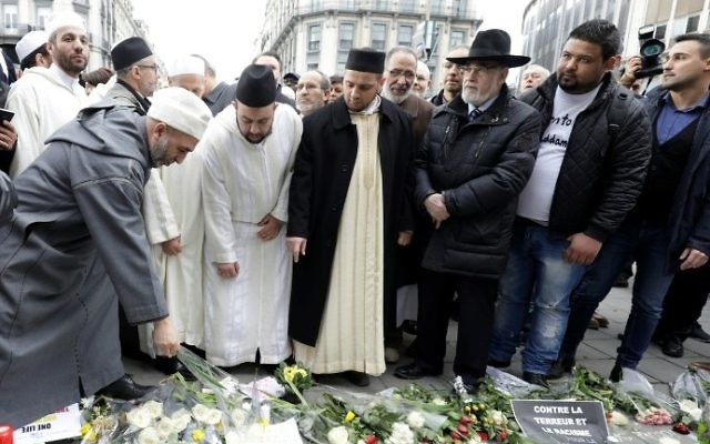 People leave flowers at a makeshift memorial following a commemorative march at La Bourse in Brussels on March 22, 2017, as Belgium marks the first anniversary of the twin Brussels attacks by Islamic extremists. (AFP Photo/Belga/Thierry Roge)