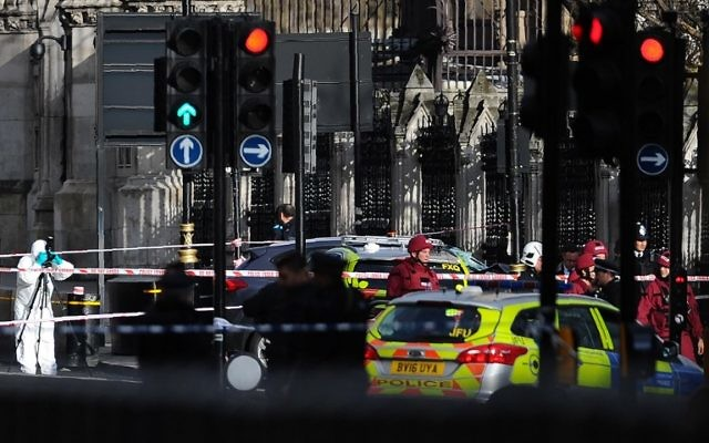 Armed police officers stand guard as forensics officers work around a grey vehicle that crashed into the railings of the Houses of Parliament in central London on March 22, 2017. (AFP Photo/Daniel Sorabji)