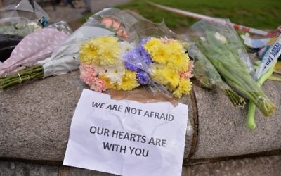 """Floral tributes with a message reading """"We are not afraid, our hearts are with you"""" are seen near a police cordon in Westminster in central London on March 23, 2017 a day after a deadly terror attack killed at least three people. (John Tallis/AFP)"""
