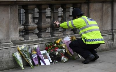A police officer lays flowers on Whitehall around a photograph of police officer Keith Palmer who was killed in the March 22 terror attack in Westminster, in Westminster near the Houses of the Parliament in central London on March 23, 2017.  (AFP/ Justin TALLIS)