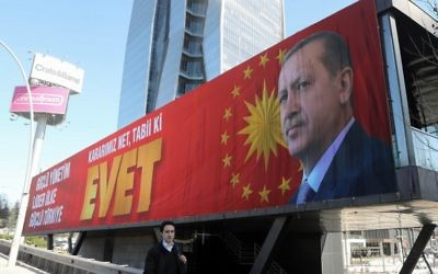 A man walks past a huge billboard picturing Turkey's President Recep Tayyip Erdogan and with an inscription which translates as 'Yes' on March 23, 2017 in Ankara. (AFP/Adem Altan)