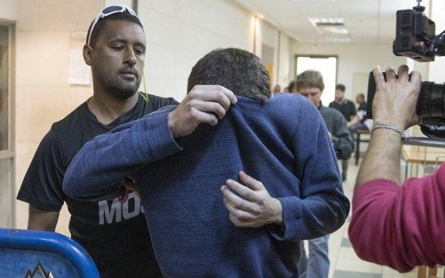 An American-Israeli Jewish teenager, center, accused of making bomb threats in the United States and elsewhere, is escorted by guards as he leaves the Israeli court in Rishon Lezion on March 23, 2017. (AFP/JACK GUEZ)