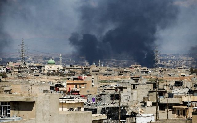 A picture taken on March 24, 2017 shows smoke plumes rising in a neighborhood in west Mosul, during an offensive by the Iraqi forces to retake the city from Islamic State (IS) group fighters. (AFP/Ahmad Gharabli)