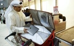 Kuwaiti social media activist Thamer al-Dakheel Bourashed puts his laptop inside his suitcase at Kuwait International Airport in Kuwait City, before boarding a flight to the United States on March 23, 2017. (AFP/Yasser Al-Zayyat)