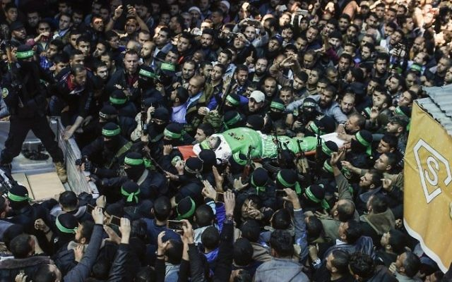 The body of Hamas terrorist Mazen Faqha is carried by members of the Izz ad-Din al-Qassam Brigades, the military wing of Hamas, during his funeral in Gaza City on March 25, 2017. (AFP/Mahmud Hams)