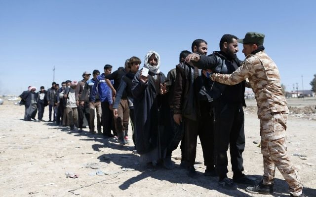 Displaced Iraqis, who fled their homes due to the ongoing fighting between government forces and Islamic State (IS) group fighters, are checked as they arrive on March 25, 2017, to be taken to camps as an ongoing operation against the jihadists continues in the city of Mosul. ( AFP PHOTO / AHMAD GHARABLI)