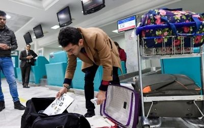 A Libyan traveler packs his laptop in his suitcase before boarding his flight for London at Tunis-Carthage International Airport on March 25, 2017.(AFP/Fethi Belaid)