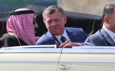 Saudi Arabia's King Salman bin Abdulaziz al-Saud and Jordanian King Abdullah II sit in a vintage car during a welcome ceremony  at the airport in the Jordanian capital Amman on March 27, 2017 ahead of the 28th Summit of the Arab League.   / AFP PHOTO / Khalil MAZRAAWI