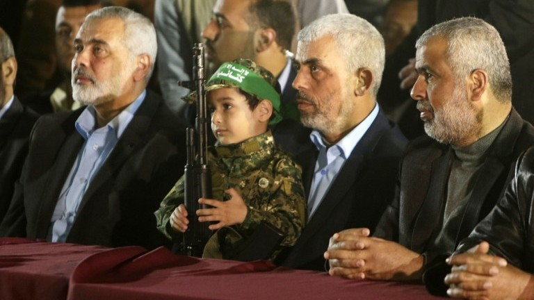 Hamas' new leader in the Gaza Strip Yahya Sinwar (2nd R) and senior political leader Ismail Haniyeh (L) sit next to the son of assassinated Hamas military leader Mazen Faqha on March 27, 2017, in Gaza City. (AFP Photo/Mahmud Hams)