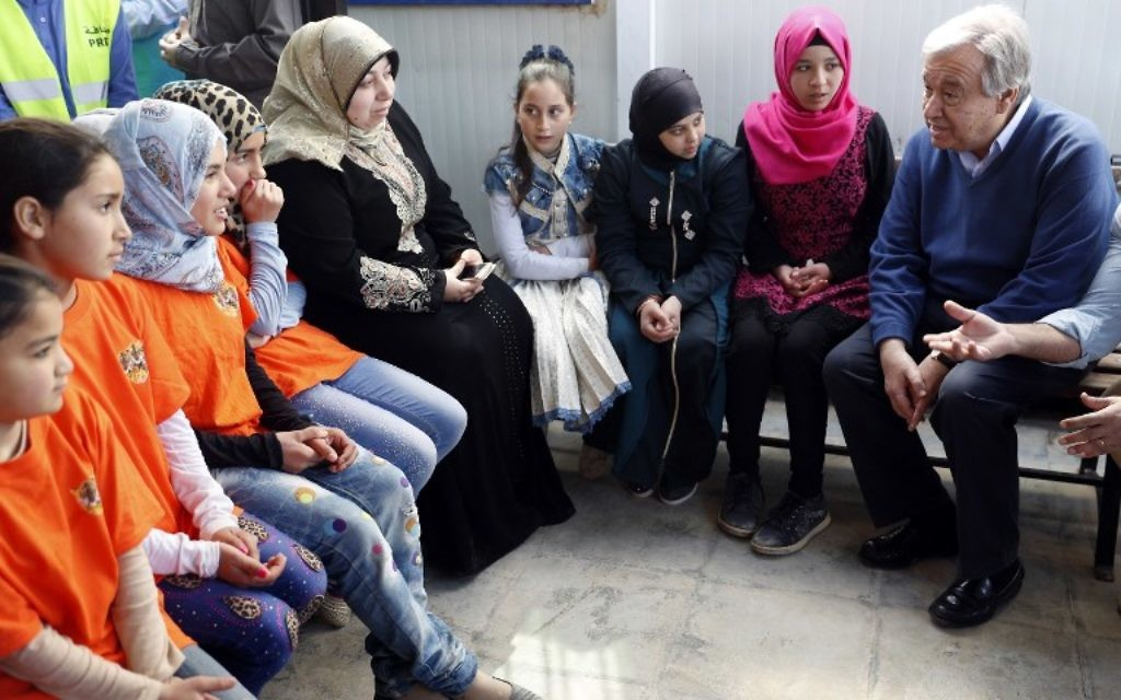 United Nations Secretary General Antonio Guterres (R) talks to Syrian women and girls during a visit to the Zaatari refugee camp which shelters some 80,000 Syrian refugees on the Jordanian border with war-ravaged Syria on March 28, 2017. (AFP Photo/Thomas Coex)