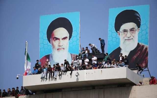 Iran soccer fans cheer beneath posters depicting supreme leaders Ruhollah Khomeini and Ali Khamenei during the 2018 World Cup qualifying match between Iran and China at the Azadi Stadium in Tehran on March 28, 2017. (AFP/ATTA KENARE)