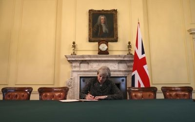 Britain's Prime Minister Theresa May, sits below a painting of Britain's first Prime Minister Robert Walpole, as she signs the official letter to European Council President Donald Tusk, invoking Article 50 and signaling the United Kingdom's intention to leave the EU, in the cabinet office inside 10 Downing Street on March 28, 2017. (AFP Photo/Pool/Christopher Furlong)