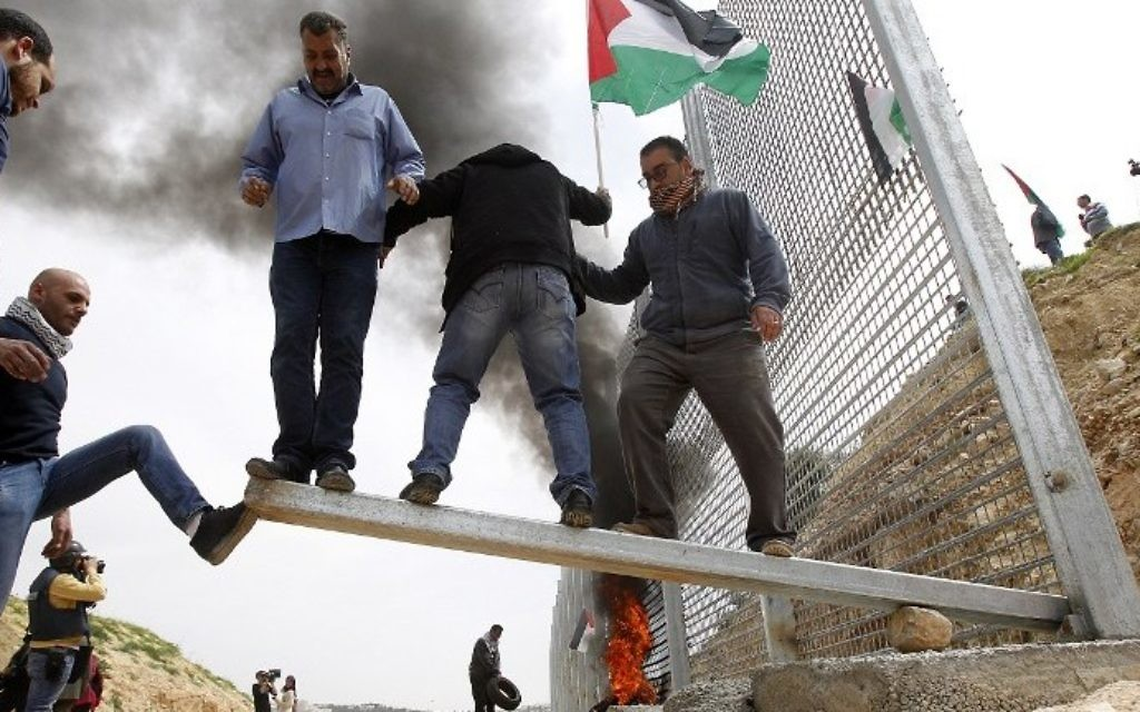 Palestinian demonstrators attempt to damage an iron fence, setup by Israeli security forces, between the Palestinian village of Beit Jala and the Jerusalem area, on March 30, 2017 during Land Day protest in the Israeli occupied West Bank. (AFP PHOTO / Musa AL SHAER)