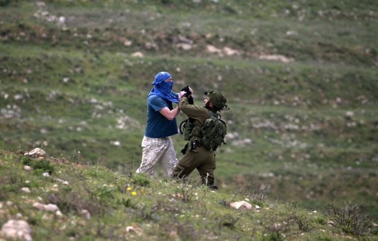 An IDF soldier scuffles with a masked Israeli settler while trying to remove him from the area of a protest by Palestinians to mark Land Day, in the village of Madama, south of Nablus in the West Bank, on March 30, 2017. (AFP/JAAFAR ASHTIYEH)
