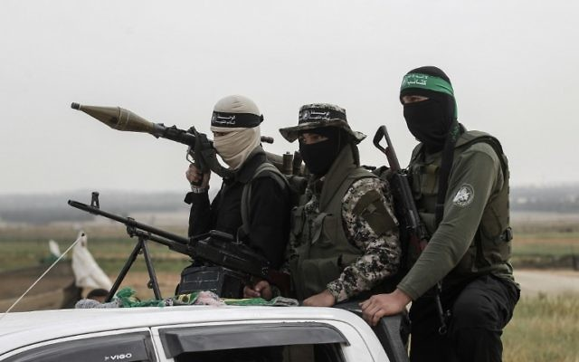 Members of the Izz ad-Din al-Qassam Brigades, the military wing of the Palestinian terror groupt Hamas, patrol during a rally to mark Land Day near the Israeli border with east Rafah in the southern Gaza Strip, March 30, 2017. (AFP/SAID KHATIB)