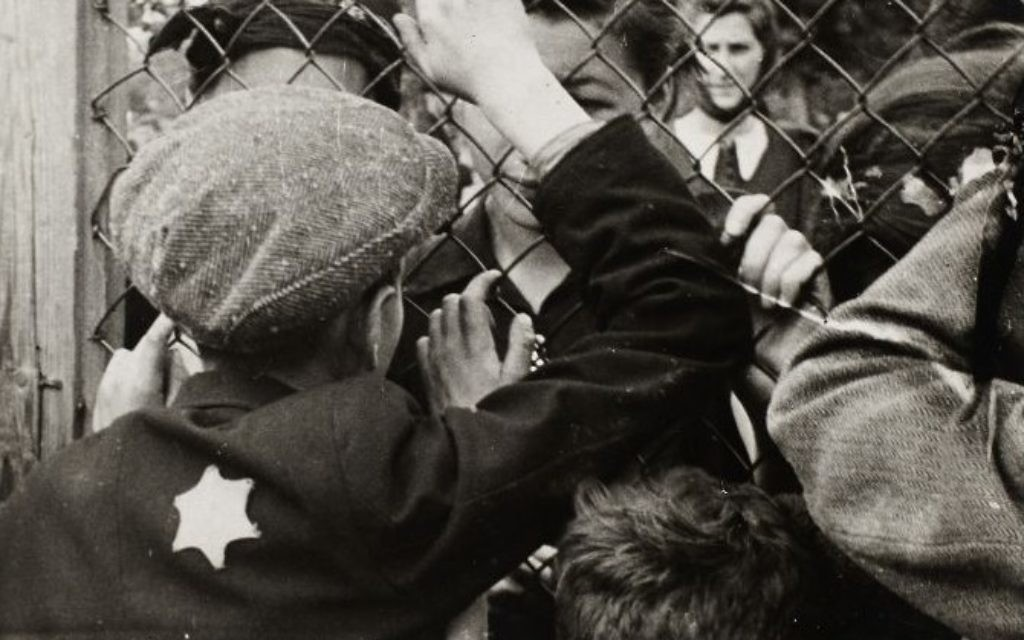 Children talking through the fence of the central prison on Czarneck Street prior to deportation. (Henryk Ross/Art Gallery of Ontario, gift from the Archive of Modern Conflict/Courtesy Museum of Fine Arts)