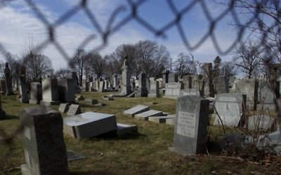 Vandalized Jewish tombstones are framed through a hole in the fence surrounding Mount Carmel Cemetery February 27, 2017 in Philadelphia, Pennsylvania. (Mark Makela/Getty Images/AFP)