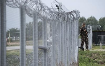 In this Sept. 21, 2016 file photo a Hungarian soldier patrols at the transit zone at Hungary's southern border with Serbia near Tompa, 169 km southeast of Budapest, Hungary. (Sandor Ujvari/MTI via AP, file)