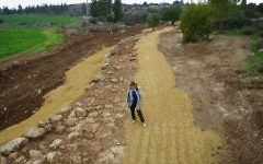 IAA archaeologist Irina Zilberbod, at a Roman road near Beit Shemesh excavated in February 2017. (The Griffin Aerial Photography Company, courtesy of the Israel Antiquities Authority)