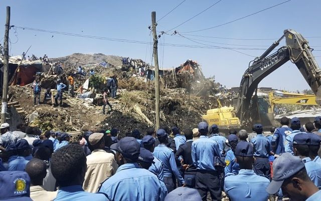 Police officers secure the perimeter at the scene of a garbage landslide, as excavators aid rescue efforts, on the outskirts of the capital Addis Ababa, Ethiopia, on Sunday, March 12, 2017. (AP Photo/Elias Meseret)