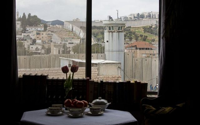 """An Israeli security watch tower is seen from one of the rooms of the """"The Walled Off Hotel"""" in the West Bank city of Bethlehem, Friday, March 3, 2017. (Dusan Vranic/AP)"""