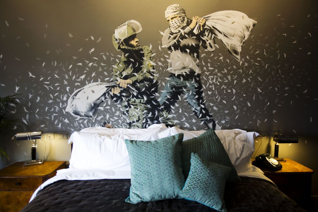 "A Banksy wall painting showing Israeli border policeman and Palestinian in a pillow fight is seen in one of the rooms of the ""The Walled Off Hotel"" in the West Bank city of Bethlehem, Friday, March 3, 2017. (AP Photo/Dusan Vranic)"