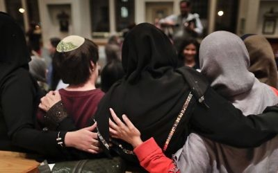In this Thursday, Feb. 16, 2017 photo, members of the Sisterhood Salaam Shalom, gather for a group photo after a unity vigil held at the Jewish Theological Seminary in New York. (AP/Julie Jacobson)