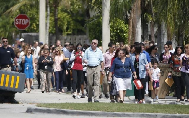 People evacuated because of a bomb threat return to the David Posnack Jewish Community Center and David Posnack Jewish Day School on Monday, Feb. 27, 2017, in Davie, Fla. (AP Photo/Wilfredo Lee)