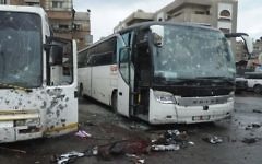 This photo released by the Syrian official news agency SANA shows blood soaked streets and several damaged buses in a parking lot at the site of an attack by twin explosions in Damascus, Syria, Saturday, March 11, 2017. (SANA via AP)