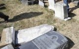 In this Monday, Feb. 27, 2017 file photo, volunteers from the Ahmadiyya Muslim Community survey damaged headstones at Mount Carmel Cemetery in Philadelphia. (AP/Jacqueline Larma)